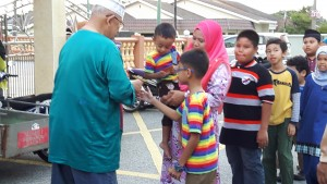 Y Bhg. Dato; Syed Azman sedang menyampaikan Duit Raya kepada kanak-kanak.